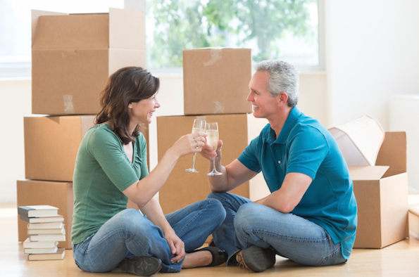 Mature Couple Toasting Champagne Flutes In New House